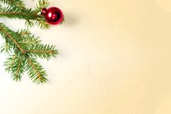 Christmas tree toy, red spherical shape lies next to a branch of spruce on a light yellow retro background