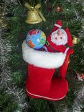 Christmas Tree Toy Santa Claus with a ball of Earth, Golden Bell, Garland, Xmas Red boot against the backdrop of a green artificia royalty free stock photo