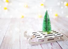 Christmas tree on the toy sled. Christmas and new year card on wooden background Stock Photos