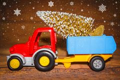 Christmas tree on toy tractor with trailer. Christmas holiday celebration concept with Snowflakes. Royalty Free Stock Photos