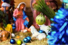 Christmas tree toy, yellow ball, on the background of a blurred image of the Christmas scene. Of the birth of Christ royalty free stock photo