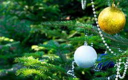 Christmas tree, Christmas toys, ball, beads. Shiny white, gold balls and silver beads on a Christmas tree closeup Royalty Free Stock Image