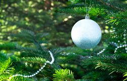 Christmas tree, Christmas toys, ball, beads. Shiny white ball and silvery beads on a Christmas tree closeup Royalty Free Stock Images