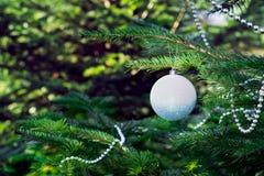 Christmas tree, Christmas toys, ball, beads. Shiny white ball and silvery beads on a Christmas tree closeup Royalty Free Stock Photos