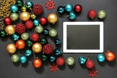 Christmas tree toys balls and ipad on dark background. Christmas tree toys, different colors balls near to the ipad with an empty space screen on a dark royalty free stock image
