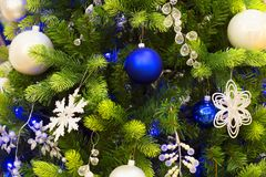 Christmas tree with toys close up. Christmas tree with a balls. Spruce branches with blue and golden balls close up. Pine branches with a snowflake, toys and Stock Photos