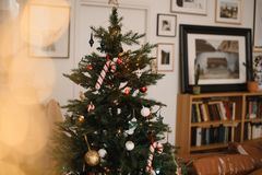 Christmas tree with toys, decorations and garlands, lights in a brown stylish room. New Year`s warm stylish interior