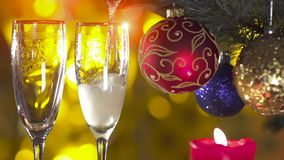 Christmas tree with two glasses and pouring. Champagne in slow motion stock footage