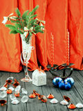Christmas tree in white decorative goblet, white gift box, blue balls, candlestick with red candles and decorative stones Stock Photography