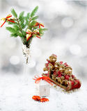 Christmas tree in white decorative goblet, white gift box, red and gold toy bears on sledge, candies and snow. On retro vintage white table on white blurred Stock Images