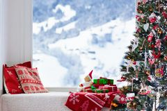 Christmas tree at window, view to snow mountains stock images