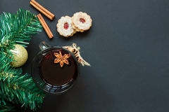 Christmas tree and wineglass of mulled wine with cookies and orange on the black table top view. Christmas tree and wineglass of hot wine with cookies and orange Stock Images