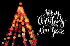 Christmas tree with wishes written in the dark background. stock photos
