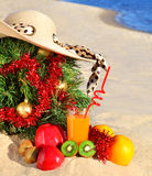 Christmas tree with woman beach hat, fresh juice and ripe fruits on sand on beach Stock Photo