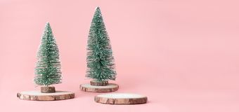 Christmas tree on wood log slice with present box on pastel pink. Studio background.Holiday festive celebration greeting card with copy space for display of royalty free stock photo