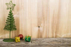 Christmas tree on a wooden background. Green metal decorative tr Stock Photos