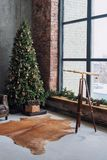 Christmas tree with wooden rustic decorations and presents under it in loft interior. Royalty Free Stock Image