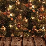 Christmas tree and wooden texture. Elegant Christmas tree decorated with baubles and fairy lights, it shines the lights dispelling the darkness of the room Stock Photography