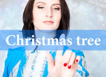 Christmas tree written on virtual screen. concept of celebratory technology in internet and networking. woman in Stock Photo