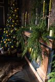 Christmas tree with yellow balls, candles and decorated fireplace stock images