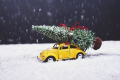 Christmas tree on yellow toy car with snow, Merry Christmas conc. Christmas tree on yellow toy car with snow stock photo