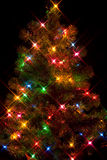 Christmas Tree1. Christmas tree on black background with starburst lighting effect Royalty Free Stock Photo