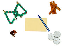 Christmas trees, candles and cinnamon with greeting card and pen. Over white stock photography