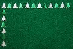 Christmas trees on felt background. Green and silver christmas trees on green felt background stock image
