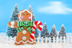 Christmas trees and gingerbread man. Decorated christmas tree forest with white picket fence in snow ready for christmas with a happy gingerbread man in the royalty free illustration