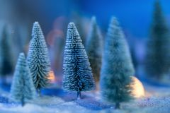 Christmas trees with heavy snow and bokeh. Miniature Christmas trees with heavy snow and bokeh background. Winter model concept with copy space for text stock photos