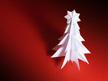 Christmas trees made of paper on red background Stock Images
