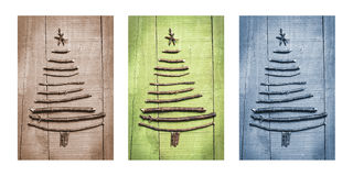 Christmas trees made of wooden branches with gifts. Triptych in brown, green and blue. Royalty Free Stock Photo