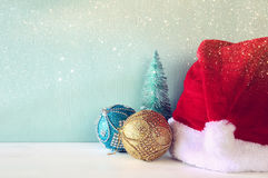 christmas trees next to santa hat. Glitter overlay Royalty Free Stock Images