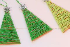 Free Christmas Trees On A Wooden Table. Creative Christmas Trees Made Of Old Cardboard Box And Cotton Yarn. Recycled Crafts Royalty Free Stock Image - 104857536