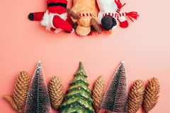 Christmas trees and pine cones border with plush toys on pink background copy space border stock images