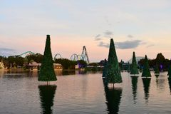 Christmas trees reflected in the lake and colorful rollercoaster on sunset background in International Drive area. royalty free stock images
