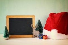 christmas trees and santa hat next to blank blackboard Royalty Free Stock Image
