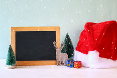 christmas trees and santa hat next to blank blackboard Stock Images