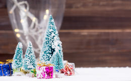 Christmas trees with snow and gift boxes - selective focus Stock Images