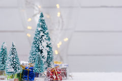 Christmas trees with snow and gift boxes - selective focus Stock Photos