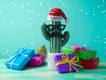 Christmas in tropical climate concept. Cactus as hipster christmas tree with santa hat and gift boxes royalty free stock image