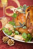 Christmas turkey on holiday table. Garnished turkey on Christmas decorated table with flute of champagne on background Stock Images