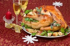 Christmas turkey on holiday table. Garnished turkey on Christmas decorated table with candle and flutes of champagne on background stock photo
