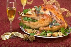 Christmas turkey on holiday table and flute of champagne. Garnished turkey on Christmas decorated table with ribbon and flutes of champagne Royalty Free Stock Photos
