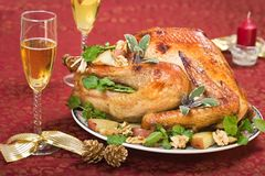 Christmas turkey on holliday table and flute of champagne. Garnished turkey on Christmas decorated table with candle and flutes of champagne stock photo