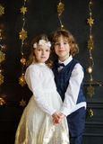 Christmas. Two festively dressed children, boy and girl, are holding hands. Stock Photography
