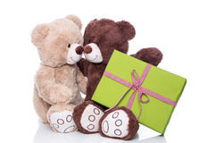 Christmas: Two isolated teddy bears in love holding a green pres Royalty Free Stock Photography