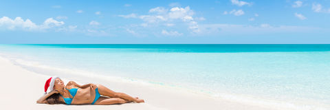 Christmas vacation beach woman banner panorama. Wide paradise beach background with Asian bikini woman lying down relaxing on white sand beach with christmas royalty free stock photography