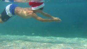 Christmas vacation at sea. Boy in Santa Claus hat swimming underwater in sea, Christmas vacation at sea concept stock video footage