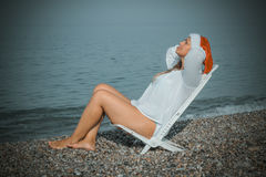 Christmas vacation. Woman in santa hat sitting on the beach Stock Image